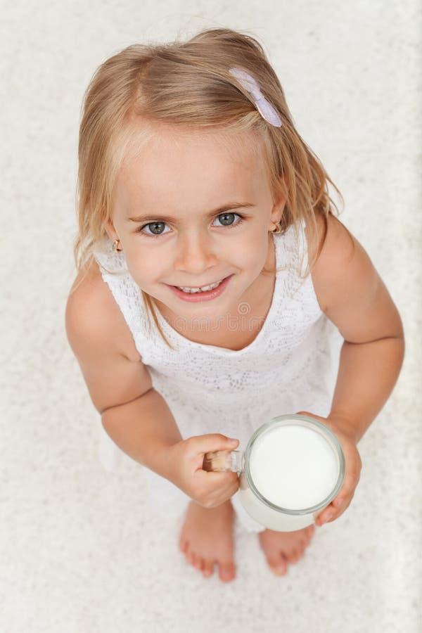 Piccola ragazza felice che tiene una tazza di latte - vista superiore immagine stock libera da diritti