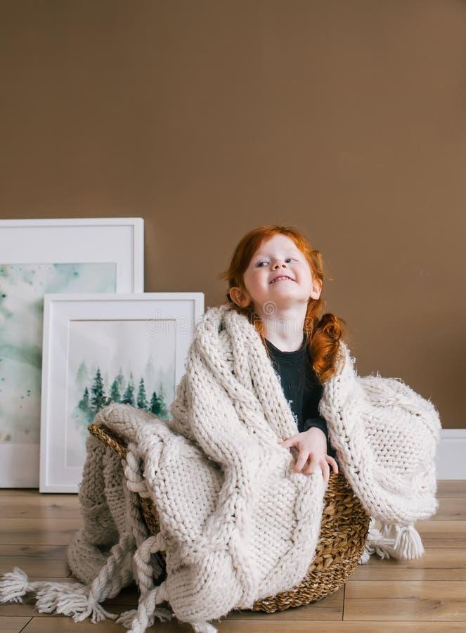 Piccola ragazza felice della testarossa che si siede nel grande canestro fotografia stock libera da diritti