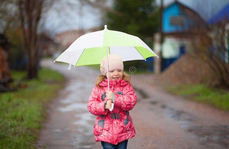 Piccola ragazza felice sorridente con l'ombrello verde in primavera immagini stock libere da diritti