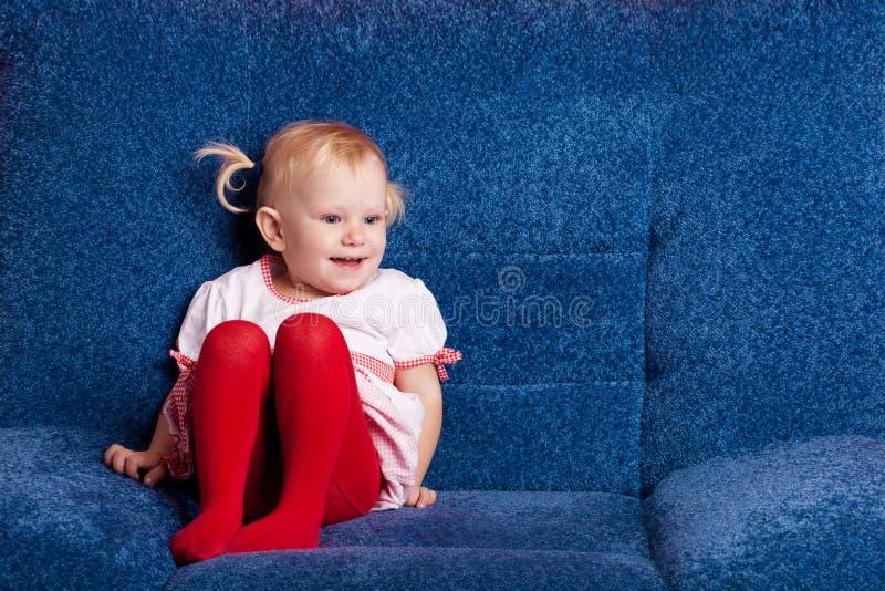 Piccola ragazza felice sul sofà immagine stock libera da diritti