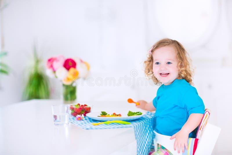 Piccola ragazza graziosa che mangia insalata per pranzo immagini stock libere da diritti