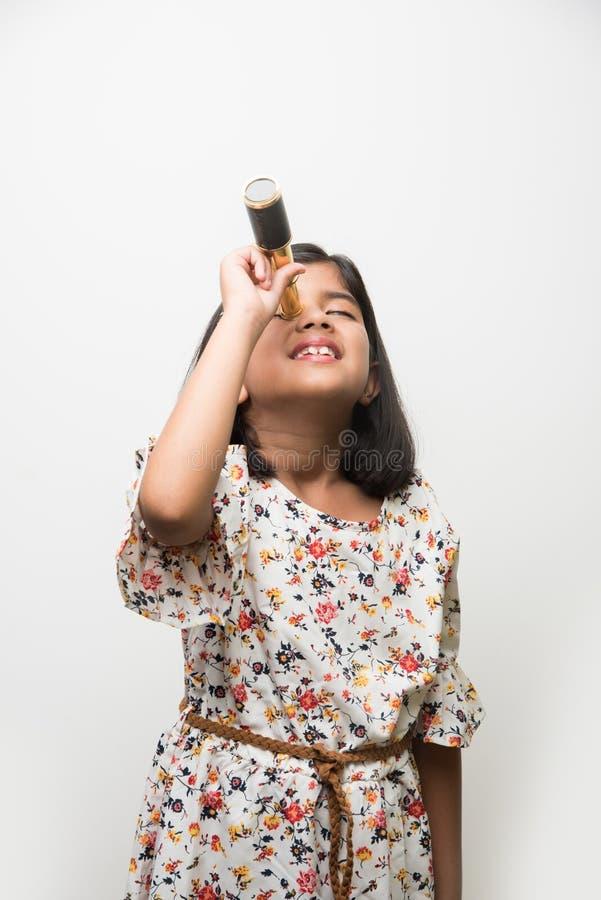 Piccola ragazza indiana che per mezzo del telescopio e studiando scienze spaziali immagine stock