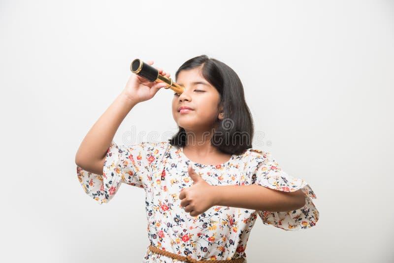 Piccola ragazza indiana che per mezzo del telescopio e studiando scienze spaziali immagini stock libere da diritti