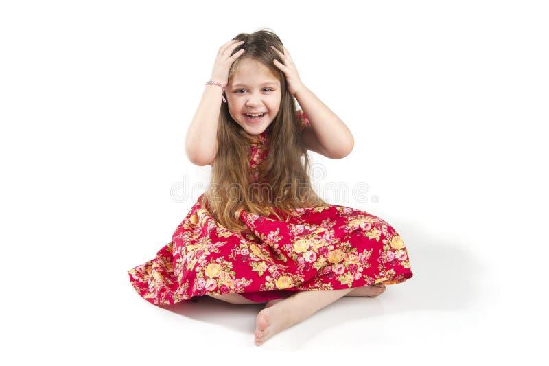 Piccola ragazza in modo divertente che giudica le sue mani dietro lei cape fotografie stock libere da diritti