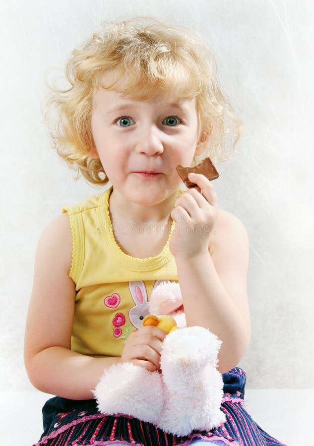 Piccola ragazza riccia bionda che mangia cioccolato immagine stock libera da diritti