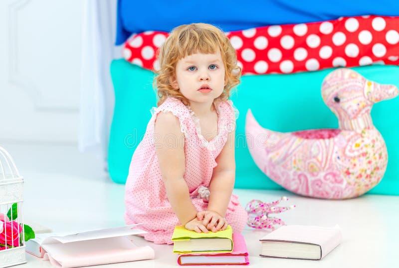 Piccola ragazza riccia sveglia in pigiami rosa che guarda il libro sedersi sul pavimento nel children& x27; camera da letto di s immagine stock libera da diritti