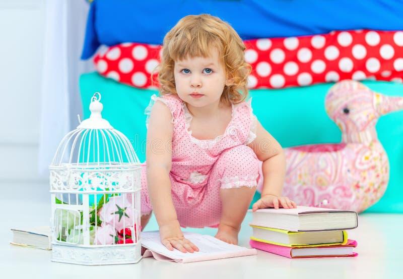 Piccola ragazza riccia sveglia in pigiami rosa che guarda il libro sedersi sul pavimento nella camera da letto dei bambini fotografie stock