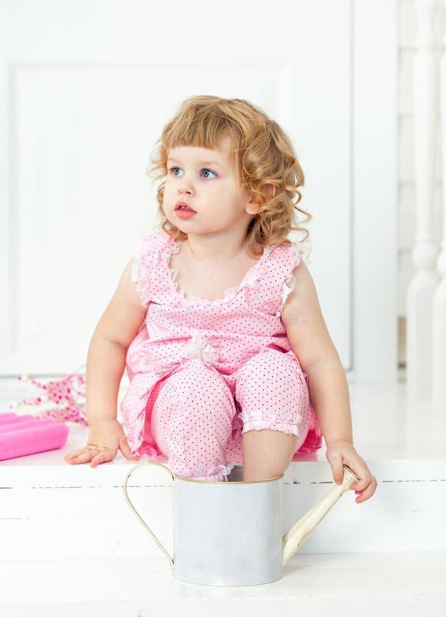 Piccola ragazza riccia sveglia in un vestito rosa con i pois che si siedono sullo stile bianco della Provenza del portico immagine stock libera da diritti