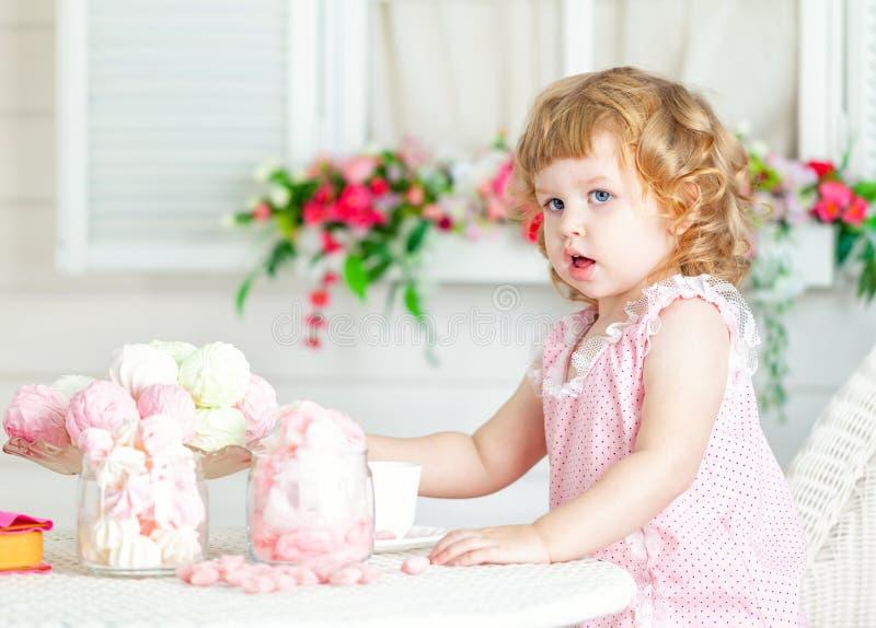 Piccola ragazza riccia sveglia in un vestito rosa con pizzo e pois che si siedono alla tavola e che mangiano i dolci differenti fotografie stock libere da diritti