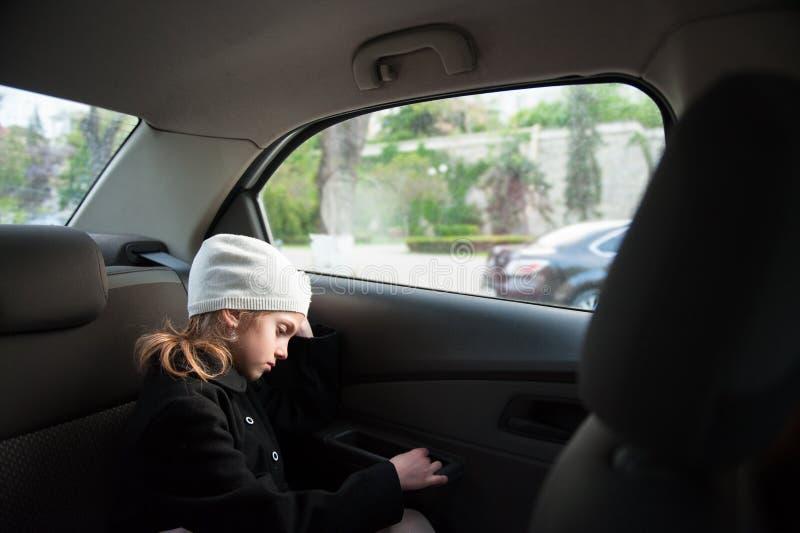 Piccola ragazza sola triste in cappello e cappotto della lana che si siedono dentro l'automobile vicino alla finestra fotografie stock libere da diritti