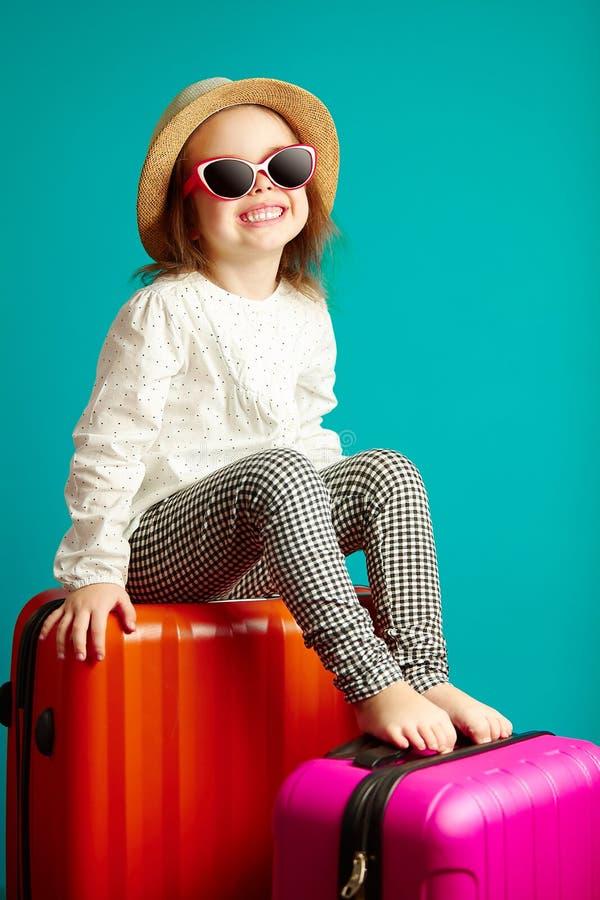 Piccola ragazza sorridente in cappello di paglia ed occhiali da sole che si siedono sulle valigie, ritratto di andare in viaggio  fotografia stock libera da diritti