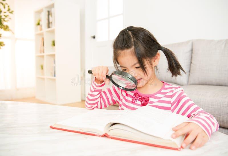 Piccola ragazza sorridente che legge un libro immagine stock