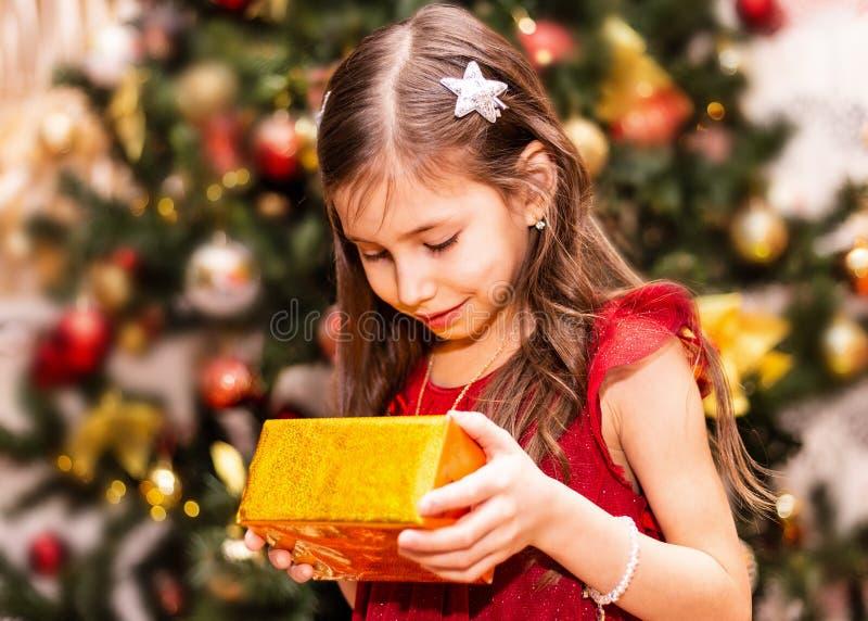 Piccola ragazza sorridente felice con il contenitore di regalo di natale immagine stock libera da diritti