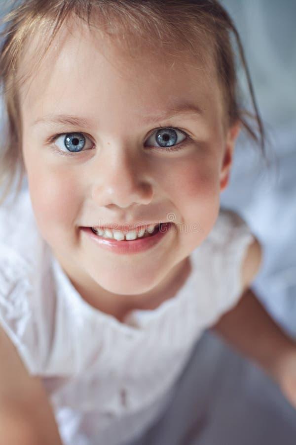 Piccola ragazza sorridente sveglia con gli occhi azzurri immagine stock libera da diritti