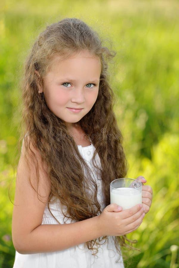 Piccola ragazza sveglia che beve un'estate all'aperto del bicchiere di latte fotografia stock libera da diritti