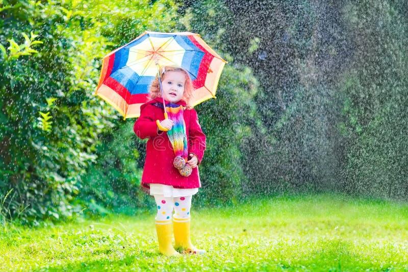 Piccola ragazza sveglia che gioca nella pioggia fotografie stock libere da diritti