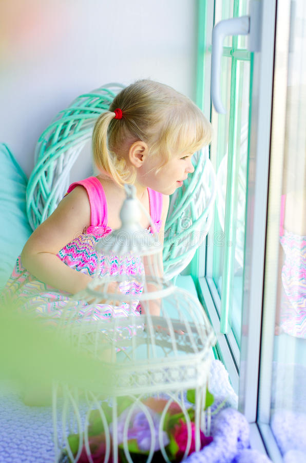 Piccola ragazza sveglia che guarda fuori finestra fotografia stock