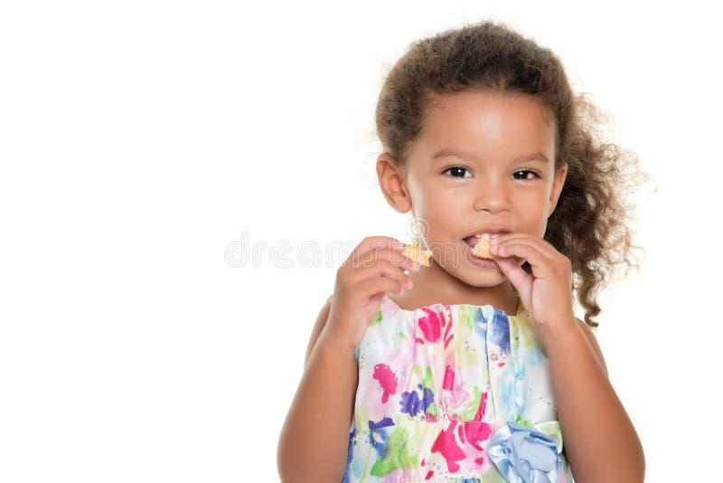 Piccola ragazza sveglia che mangia un biscotto immagini stock libere da diritti