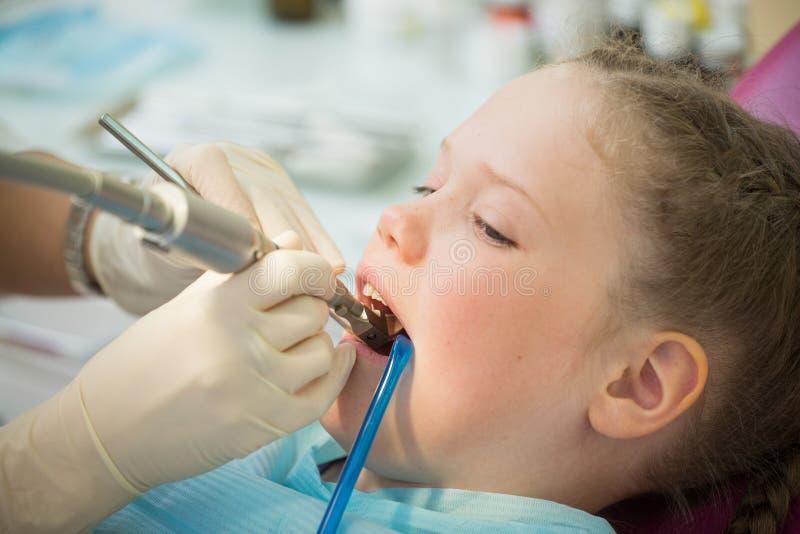 Piccola ragazza sveglia che si siede nella sedia alla clinica del dentista durante il controllo ed il trattamento dentari, ritrat fotografia stock libera da diritti