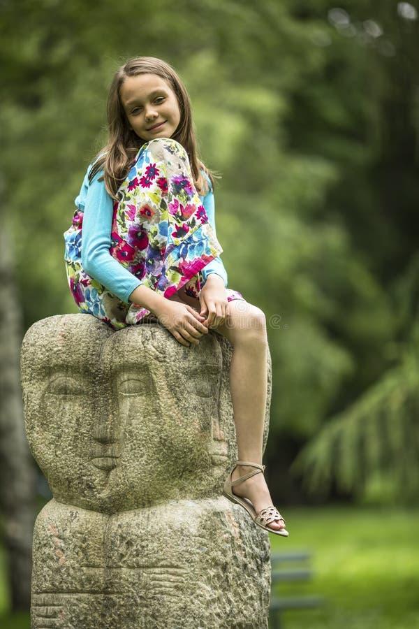 Piccola ragazza sveglia che si siede su un totem di pietra nel parco Camminata fotografia stock libera da diritti