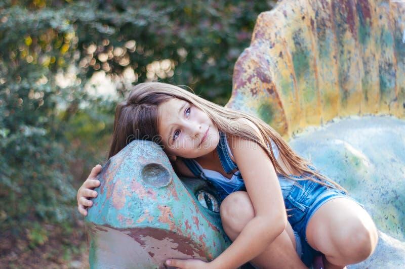 Piccola ragazza sveglia che si siede su una statua del dinosauro di estate del parco immagini stock
