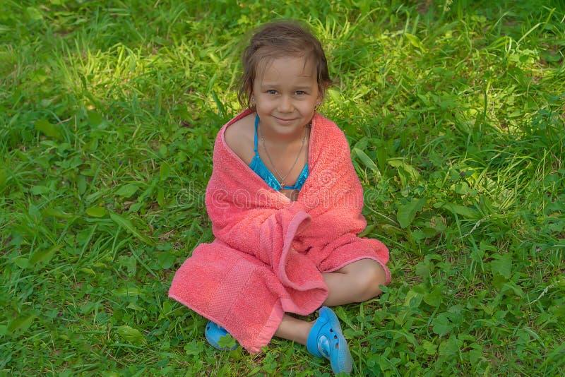 Piccola ragazza sveglia che si siede sull'erba in un asciugamano rosa dopo il nuoto nello stagno ed avere sorriso immagini stock