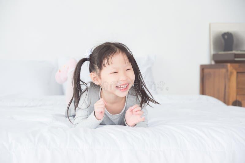 Piccola ragazza sveglia che si trova sul letto e sui sorrisi immagine stock