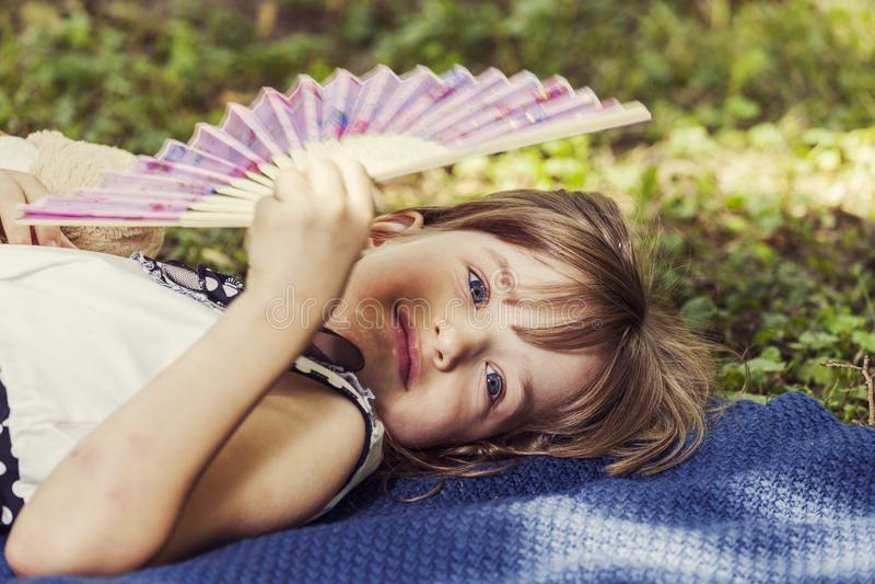 Piccola ragazza sveglia che si trova sull'erba e che tiene un ventaglio immagini stock