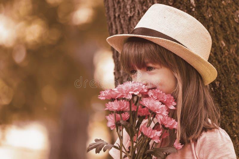 Piccola ragazza sveglia che tiene un mazzo dei fiori immagini stock