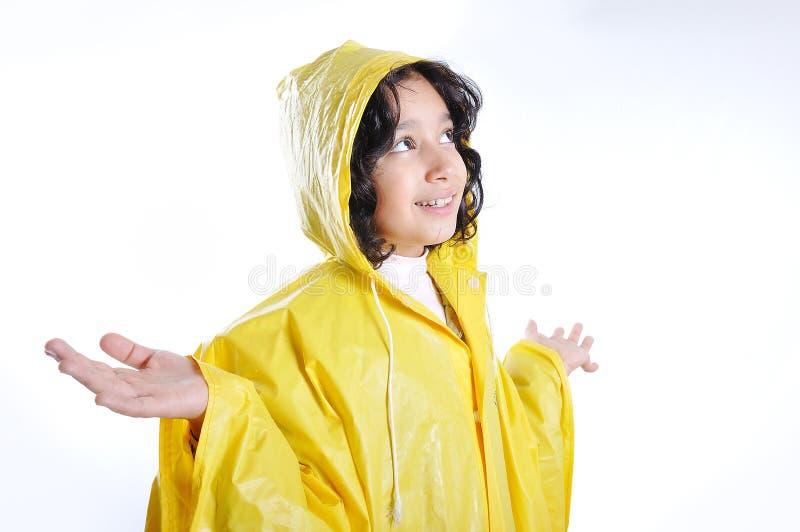 Piccola ragazza sveglia con il cappuccio giallo fotografia stock