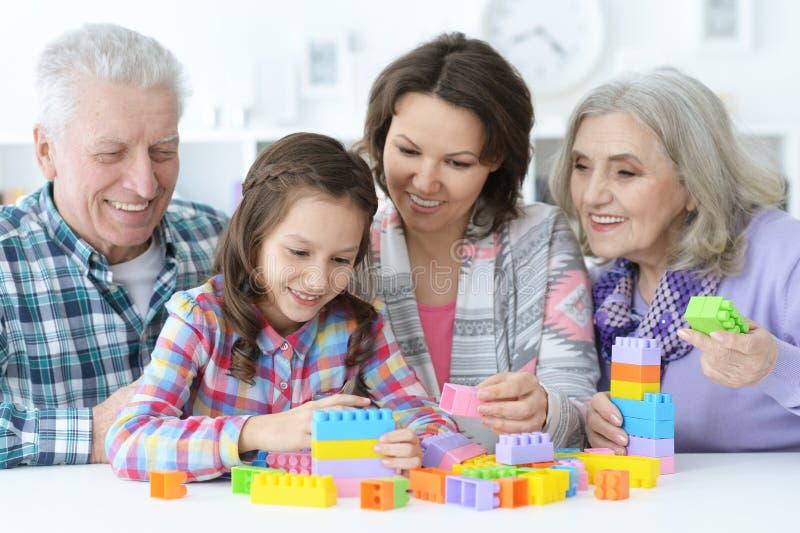 Piccola ragazza sveglia con la madre ed i nonni che giocano insieme fotografie stock libere da diritti