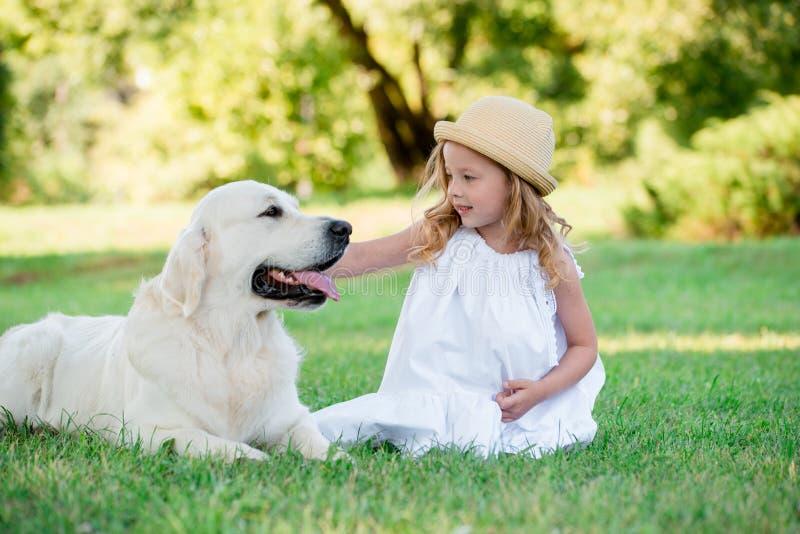 Piccola ragazza sveglia del bambino che gioca con il suo grande cane da pastore bianco Fuoco selettivo immagini stock libere da diritti