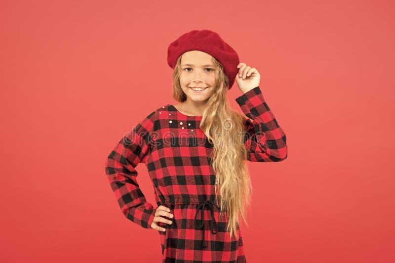 Piccola ragazza sveglia del bambino con capelli biondi lunghi che posano nel fondo rosso del cappello del berretto e del vestito  immagini stock
