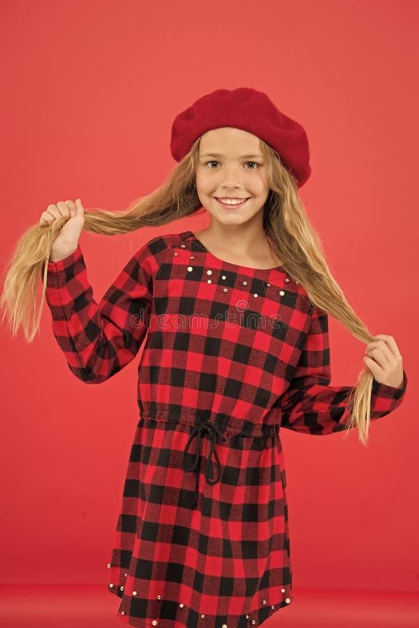 Piccola ragazza sveglia del bambino con capelli lunghi che posano nel fondo rosso del cappello Come portare berretto francese Isp immagine stock libera da diritti
