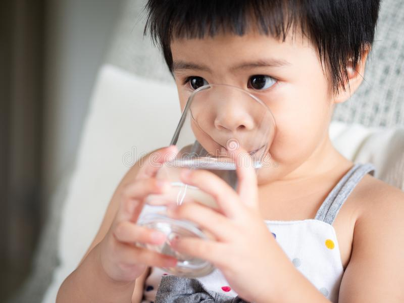 Piccola ragazza sveglia felice che tiene un vetro e che beve l'acqua C immagini stock
