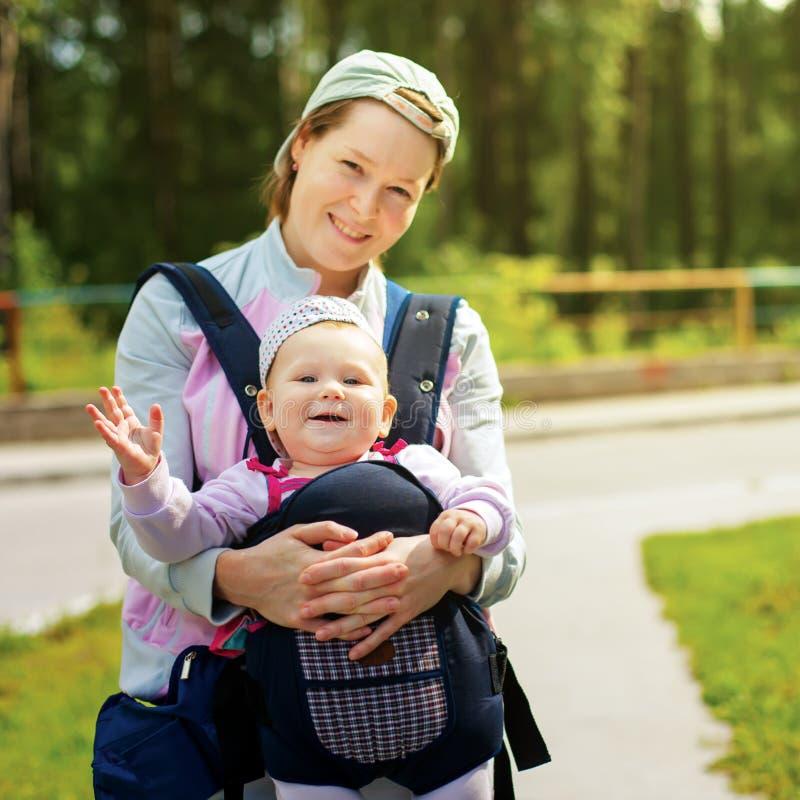Piccola ragazza sveglia in imbracatura. La mano del ` s della madre la tiene. Ora legale fotografie stock libere da diritti