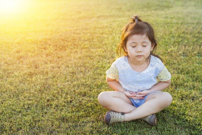 Piccola ragazza sveglia tailandese asiatica che fa meditazione e che pratica Yog fotografie stock libere da diritti