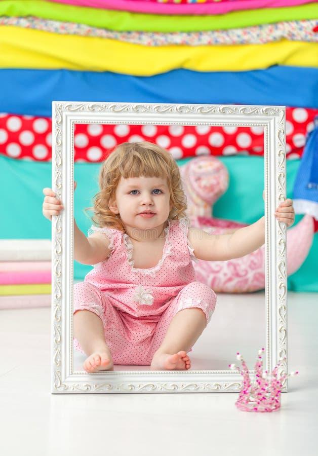 Piccola ragazza sveglia in un vestito rosa che si siede sul pavimento e che sorride sopra la struttura bianca di legno immagini stock libere da diritti