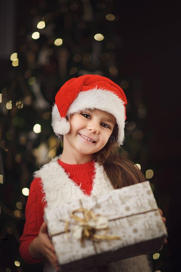 piccola ragazza sveglia vicino all'albero di Natale che tiene scatola attuale fotografie stock libere da diritti