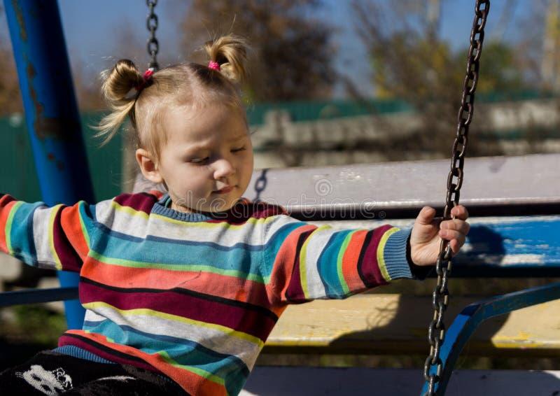 Piccola ragazza triste su un'oscillazione nel parco immagini stock libere da diritti