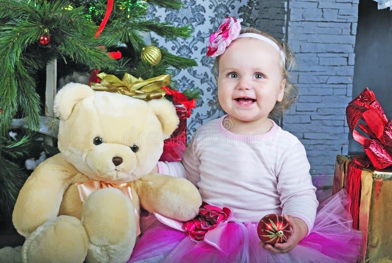 Piccola ragazza vicino all'albero di abete del nuovo anno fotografia stock libera da diritti