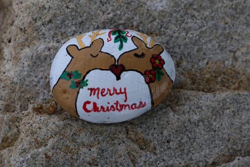 Piccola roccia dipinta con baciare di due renne immagine stock