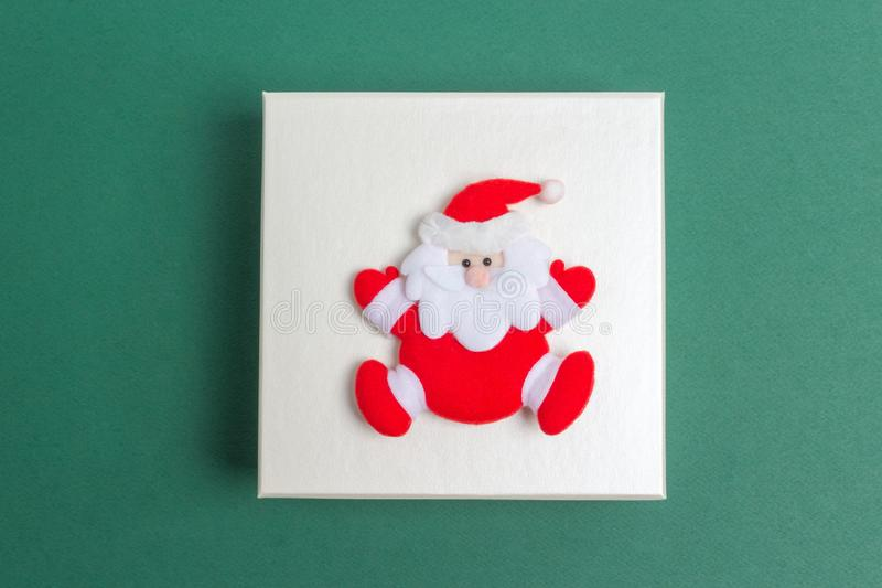 Piccola Santa Claus su un contenitore di regalo di giorno di Natale immagini stock