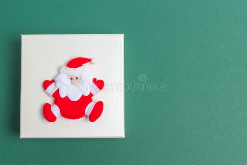 Piccola Santa Claus su un contenitore di regalo di giorno di Natale fotografie stock libere da diritti