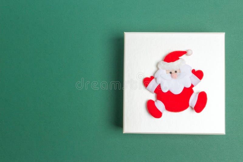Piccola Santa Claus su un contenitore di regalo di giorno di Natale fotografia stock