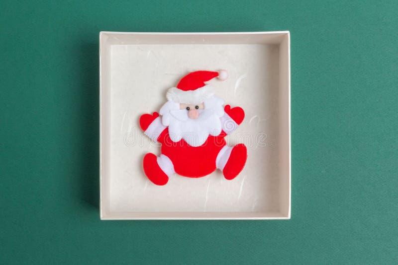 Piccola Santa Claus in un contenitore di regalo di giorno di Natale fotografia stock