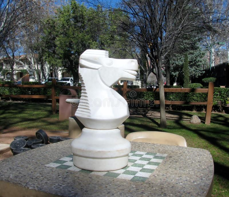 Piccola scacchiera e grande cavallo di scacchi immagine stock