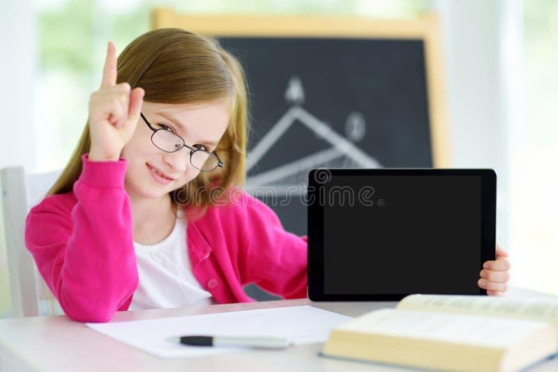 Piccola scolara astuta con la compressa digitale in un'aula immagini stock
