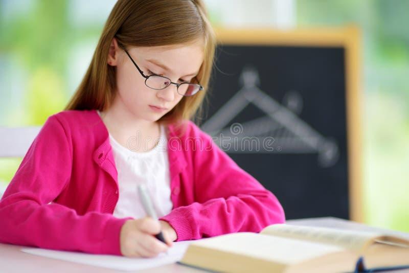 Piccola scolara astuta con la penna e libri che scrivono una prova in un'aula immagini stock