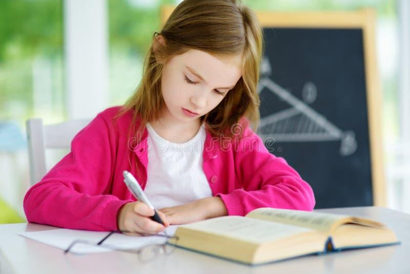 Piccola scolara astuta con la penna e libri che scrivono una prova in un'aula Bambino in una scuola elementare immagini stock libere da diritti